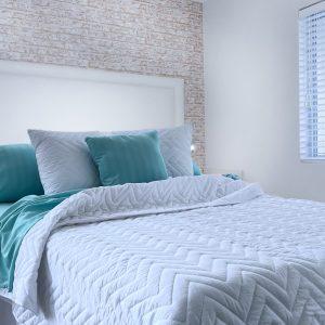Habitacion con cama almohadones y cover queen color blanco