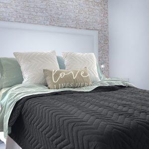 Habitacion con cama almohadones y quilt color negro