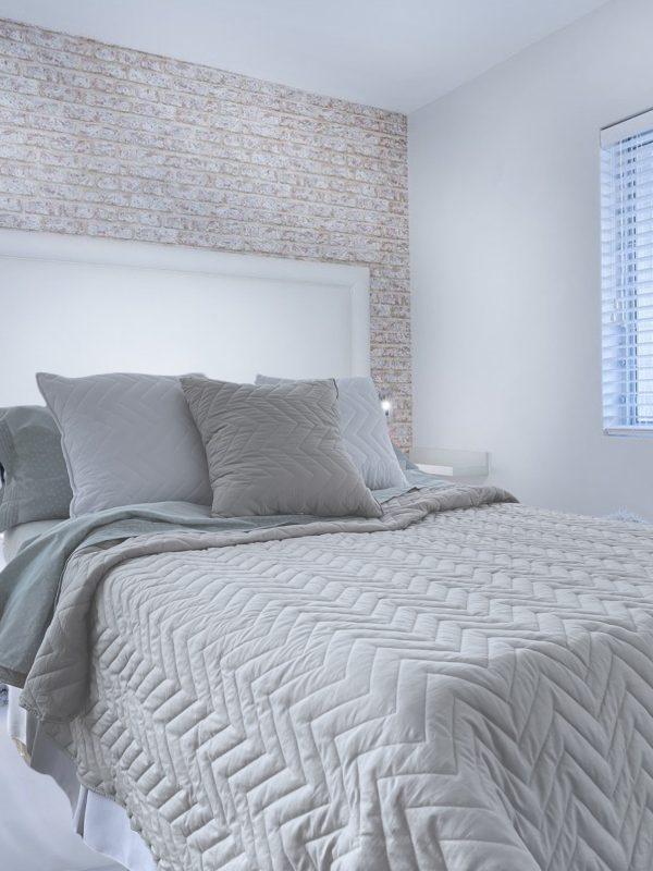 Habitacion con cama almohadones y quilt color vison